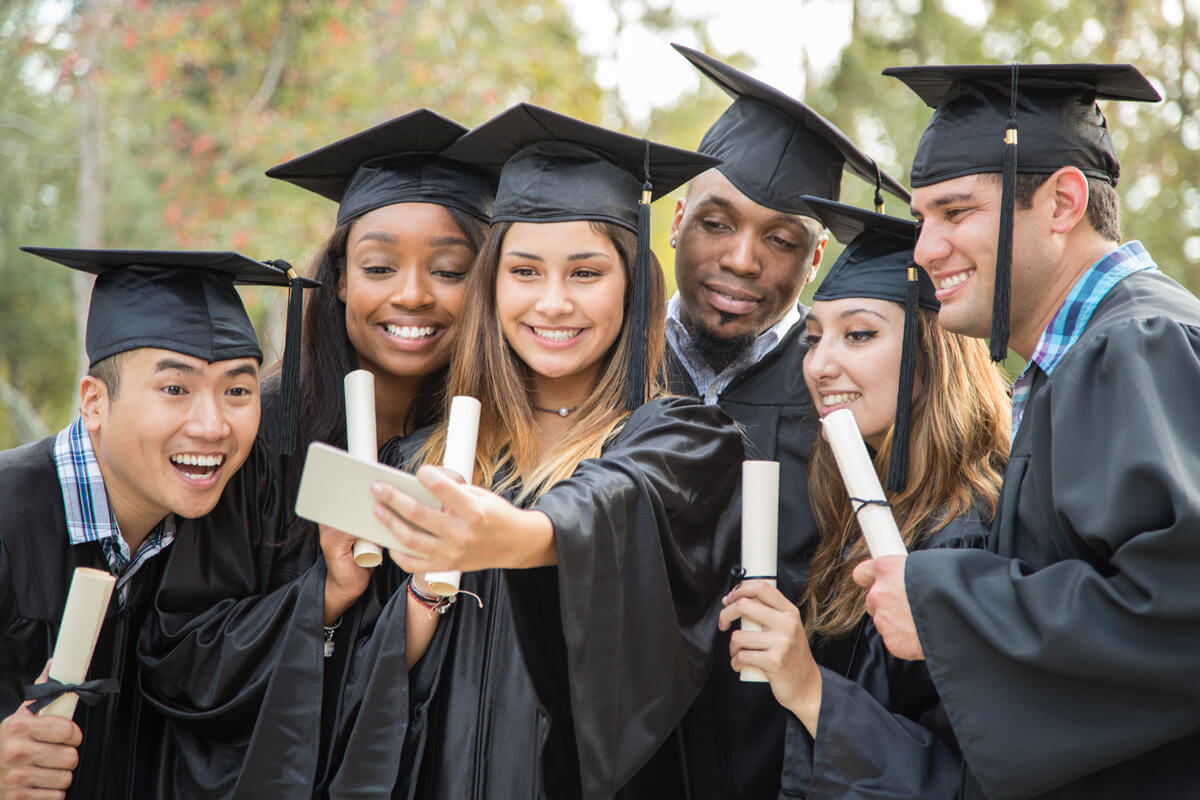 happy college graduates posing for selfie
