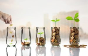 hand placing coins into jar, series of jars in increasing trend with coins and plant growth