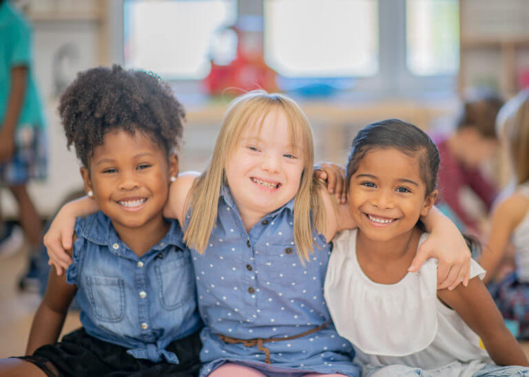 special needs girl with two friends, smiling