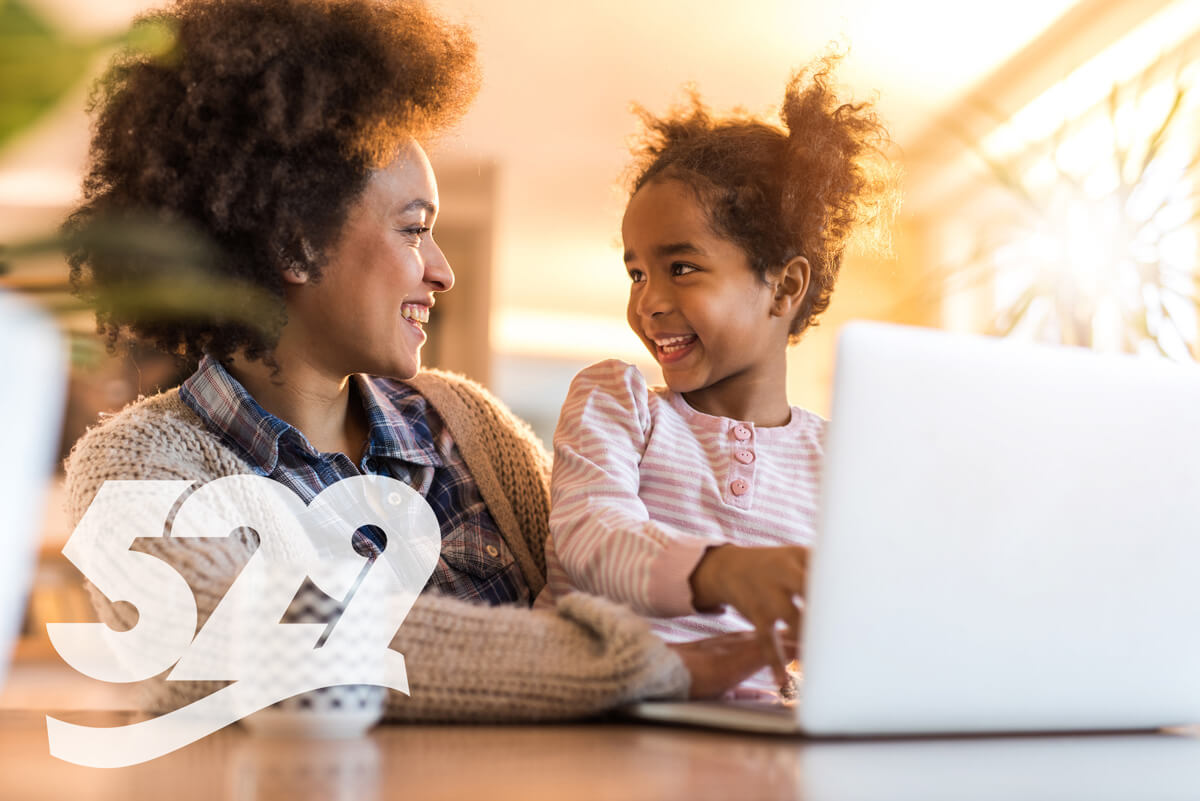 Mother and daughter smiling, using laptop, 529 logo